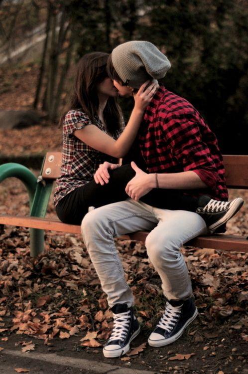 pareja de novios besandose sobre una banca en el parque