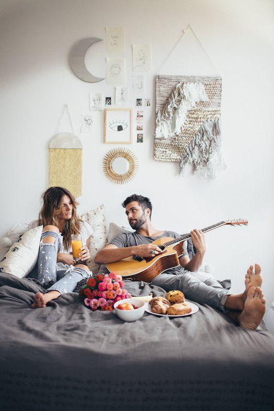 pareja relajada en cama comiendo y tocando guitarra