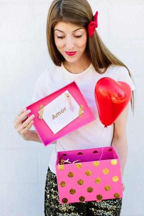 chica con una caja de regalo y globos