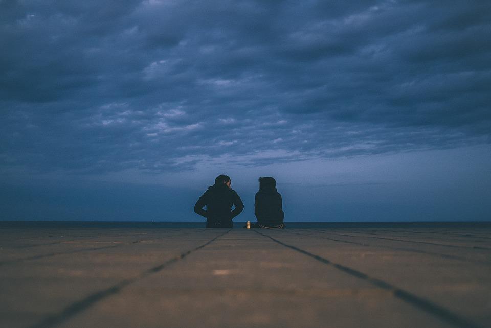 pareja sentados bajo un cielo a punto de oscurecer