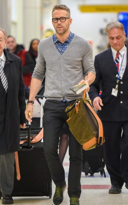 hombre con lentes caminando en aeropuerto