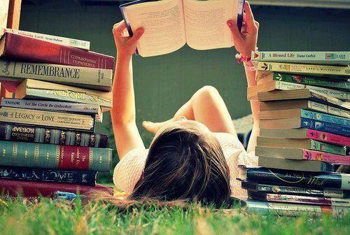 chica acostada en el pasto con muchos libros