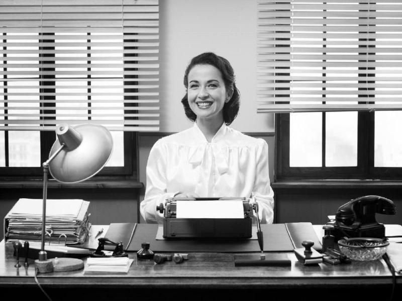 secretaria en su escritorio mostrando una sonrisa