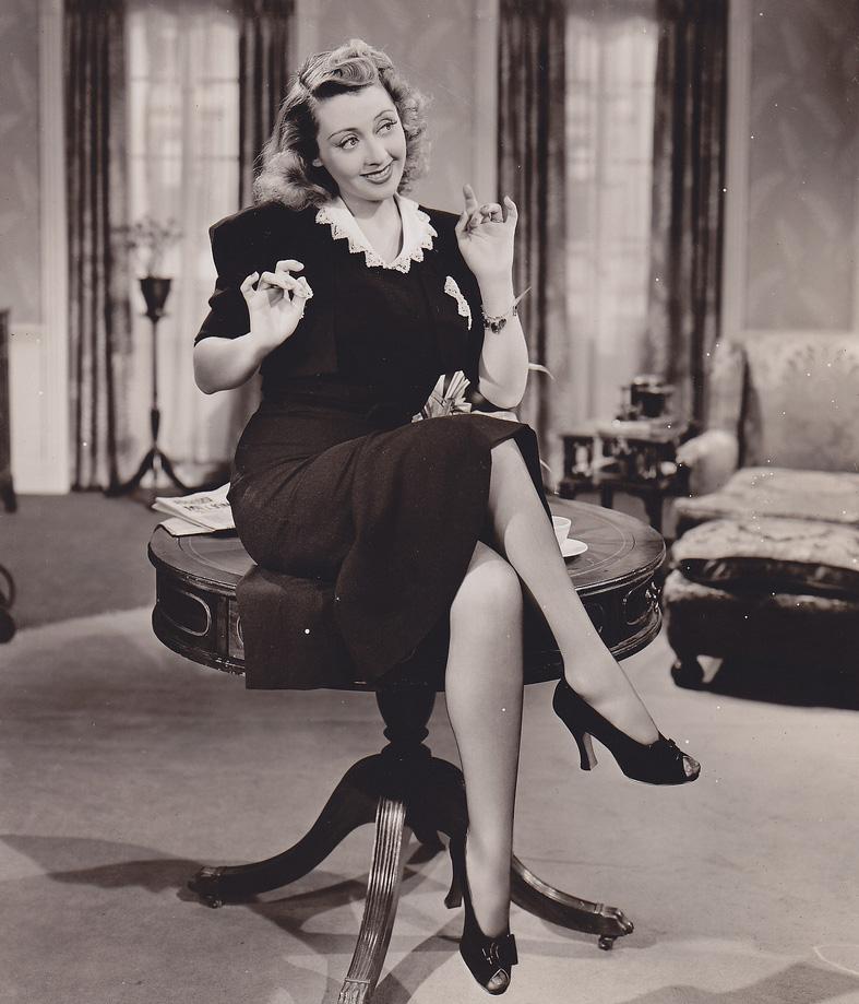 secretaria sentada sobre la mesa cruzando las piernas