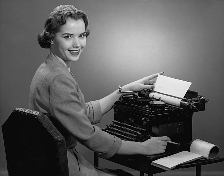 secretaria frente a su maquina de escribir sonriendo