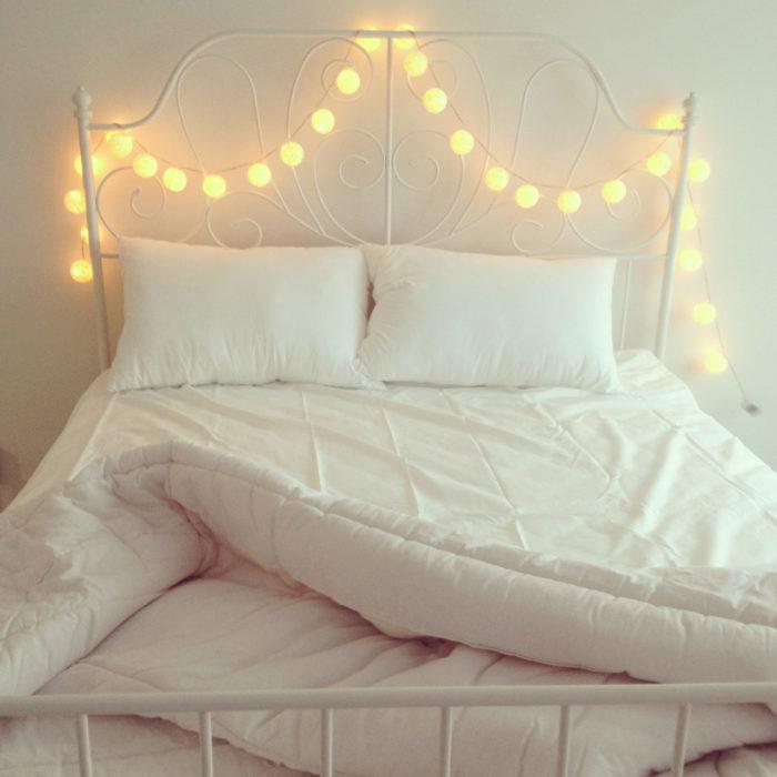cama con sabanas blancas y luces