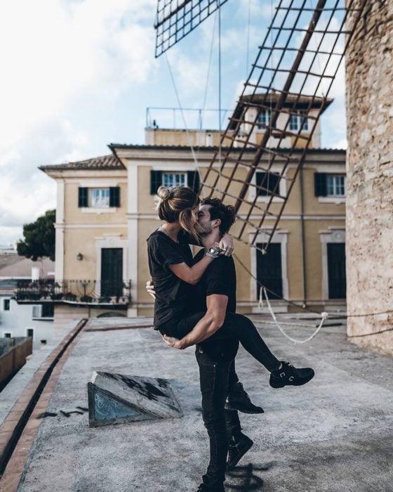 hombre carga a mujer y la besa