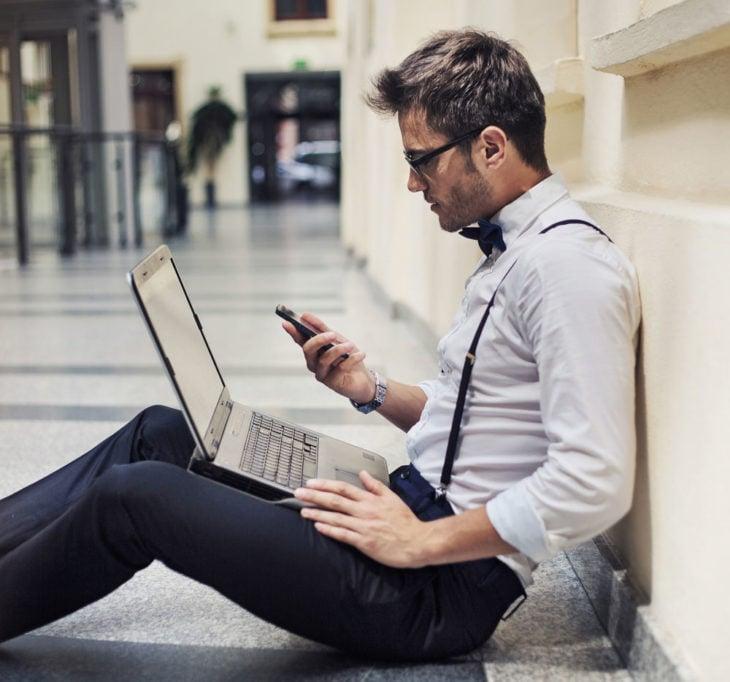 chico con lap top y teléfono en mano