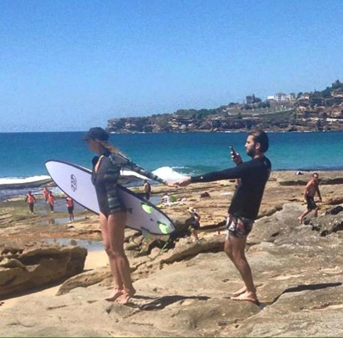 hombre tomando foto a mujer con tabla de surf