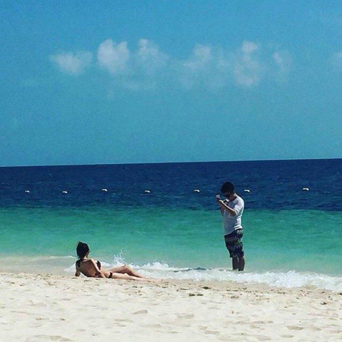 mujer acostada en la playa y hombre tomando foto