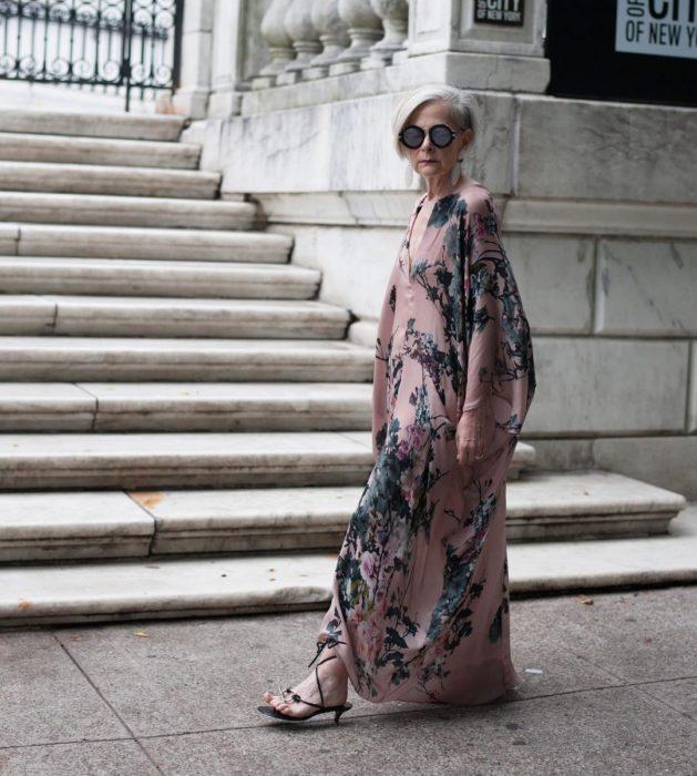 mujer con canas y vestido largo rosa