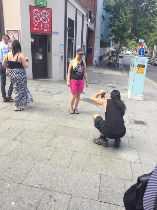 hombre agachado tomando foto a chica rubia