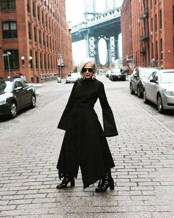 mujer con traje netro y canas