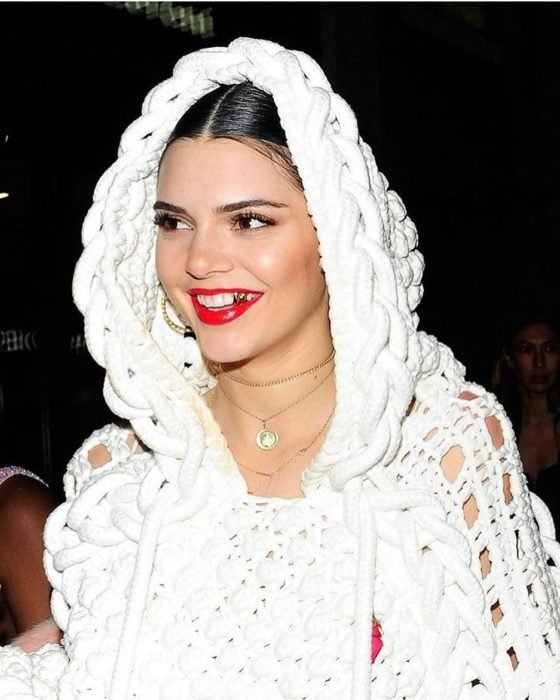 mujer blanca con cabello negro y abrigo blanco