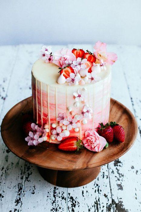 Pastel de vainilla decorado con flores naturales y fresas silvestres