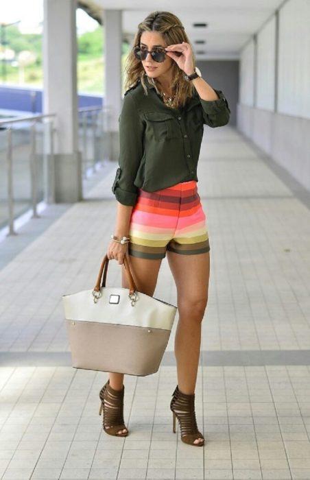 mujer con shorts de colores y camisa verde