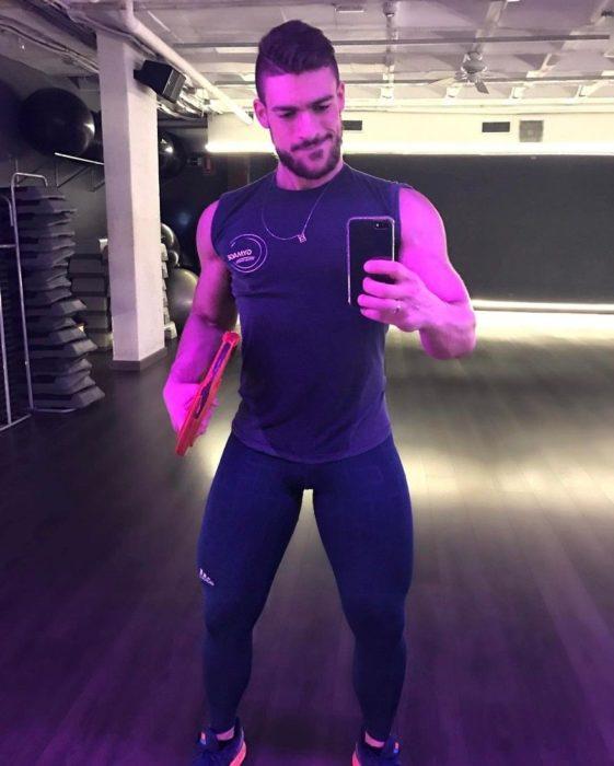 hombre con mallas y camisa en gym