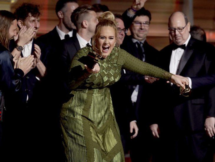 mujer rubia en vestido verde recibiendo premio