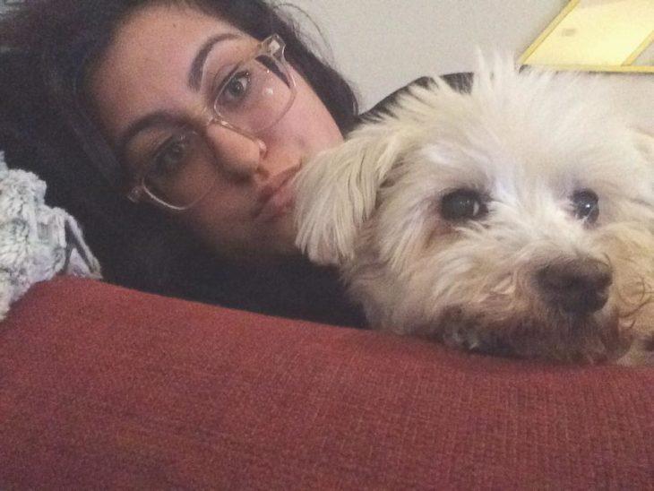 Chica que rescató a un perro sentada junto a él