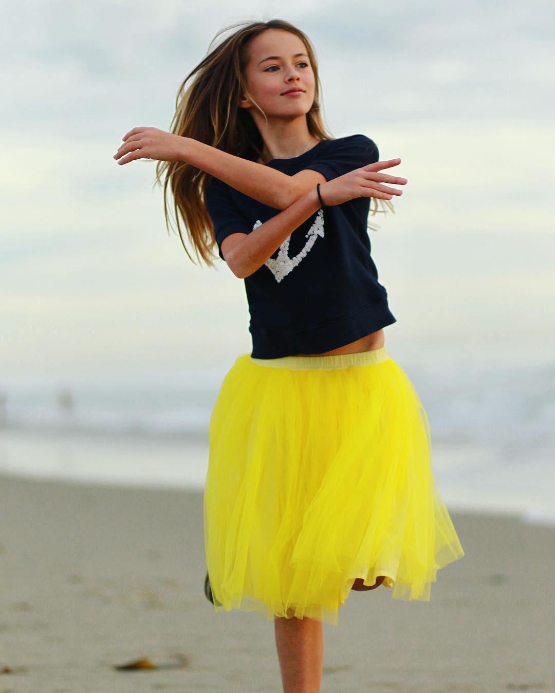 Kristina pimenova en la playa con falda amarilla