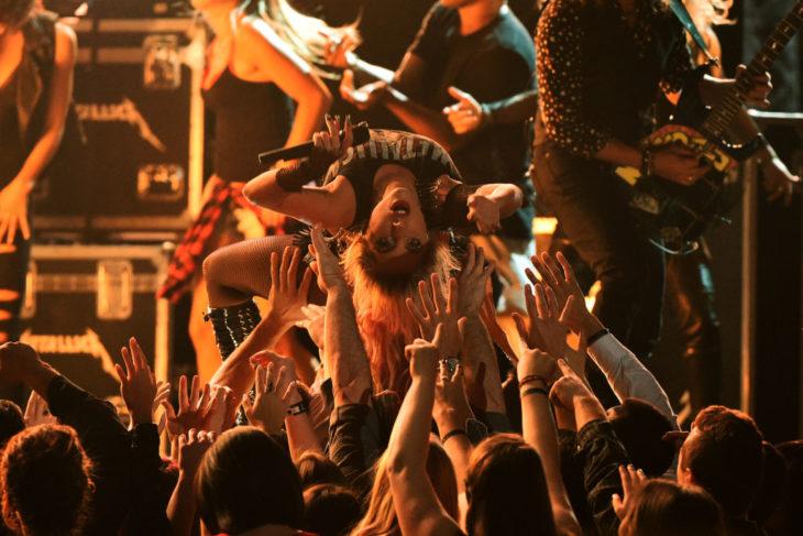 Lady gaga saltando entre la multitud durante un concierto
