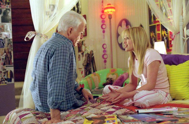 Padre e hija conversando mientras están sentados en la cama