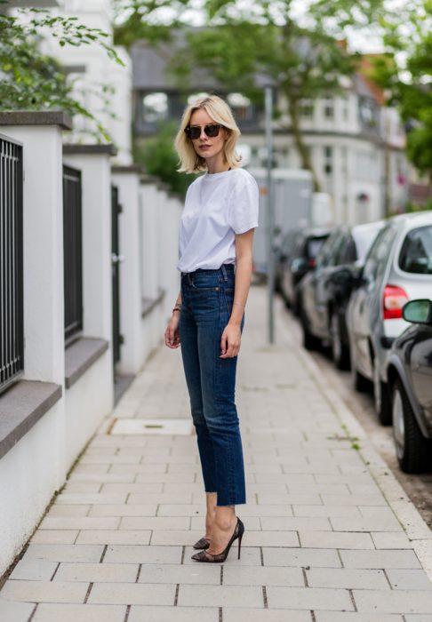 Chica usando pantalones de mezclilla y blusa blanca