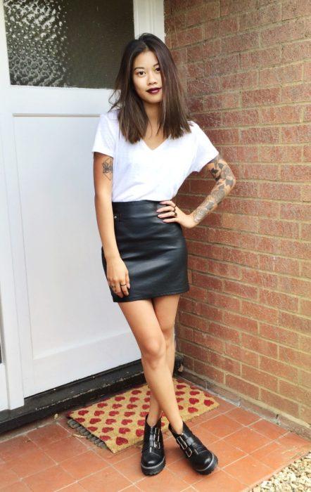 Chica usando una falda negra y blusa blanca