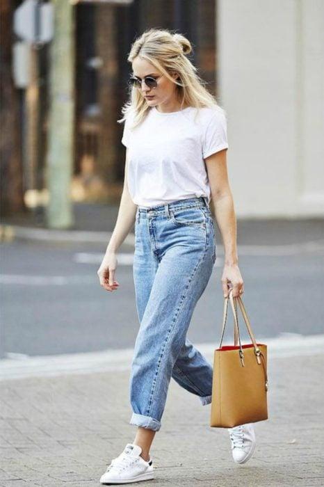 Chica usando una blusa blanca y pantalón de mezclilla