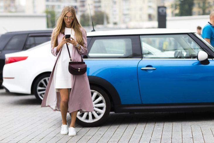 Chica usando un vestido blanco y abrigo color rosa