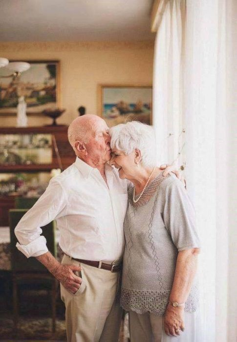 Pareja de abuelitos abrazados frente a una ventana