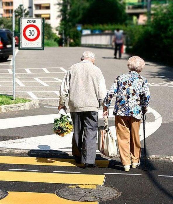 Pareja de abuelitos tomados de las manos caminando por el centro