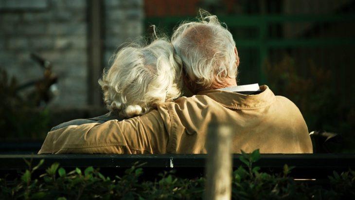 Pareja de abuelitos abrazados sentados de espaldas