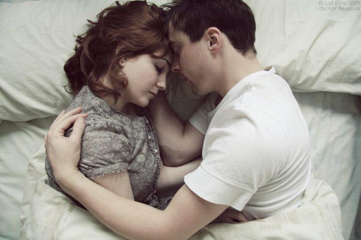 Pareja de novios recostados abrazados