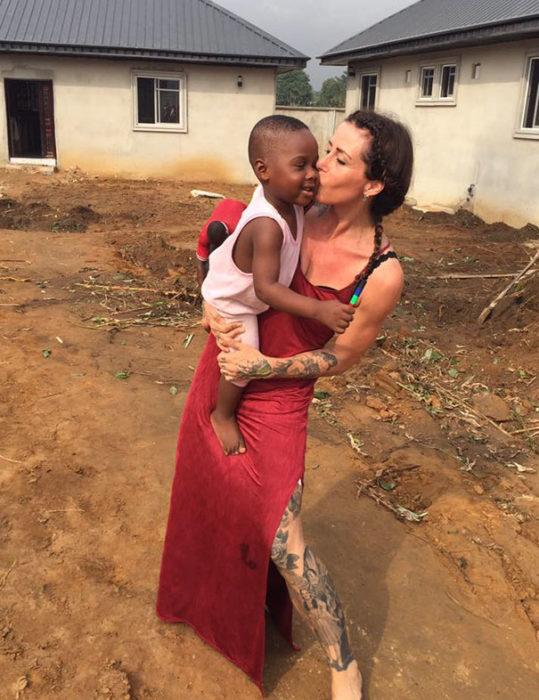 Niño rescatado de morir de hambre abrazando a la mujer que lo rescató