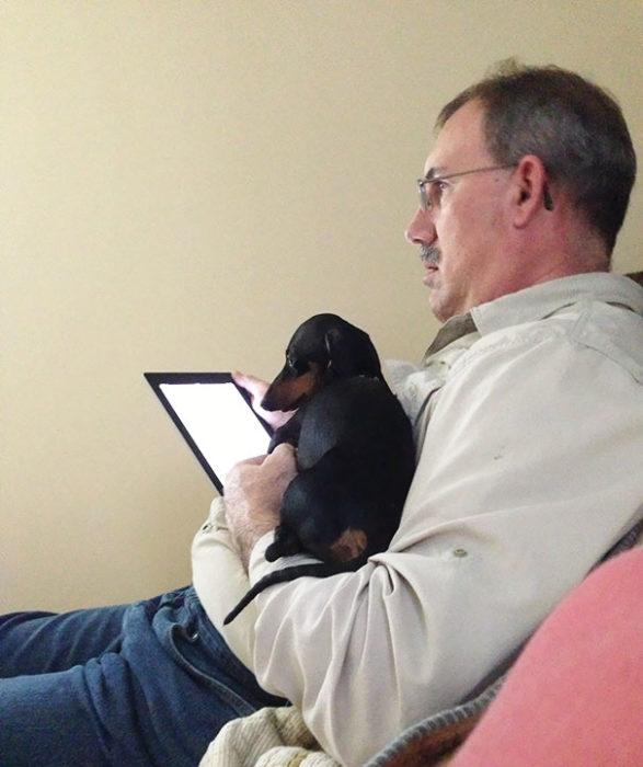 Hombre viendo su tablet junto a su perro
