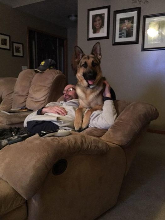 Hombre en el sofá junto a su perro viendo televisión