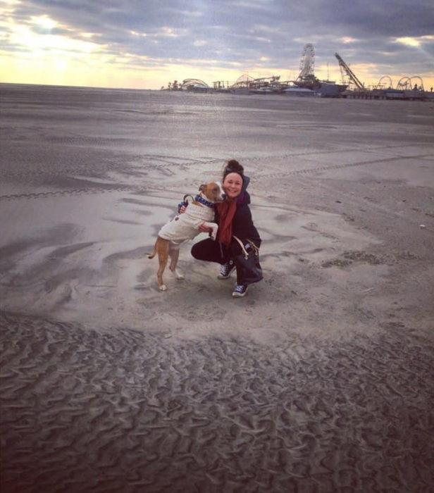 Perro y su dueña en una playa