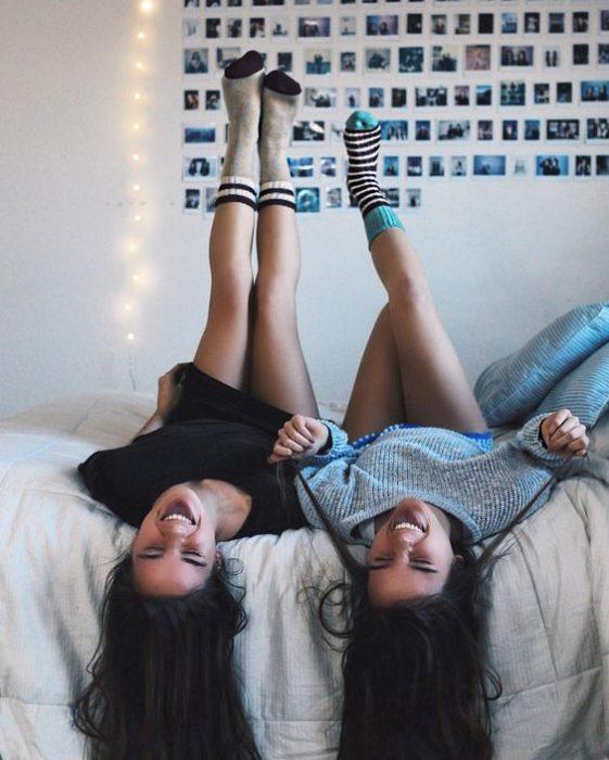 Chicas recostadas en la cama riendo