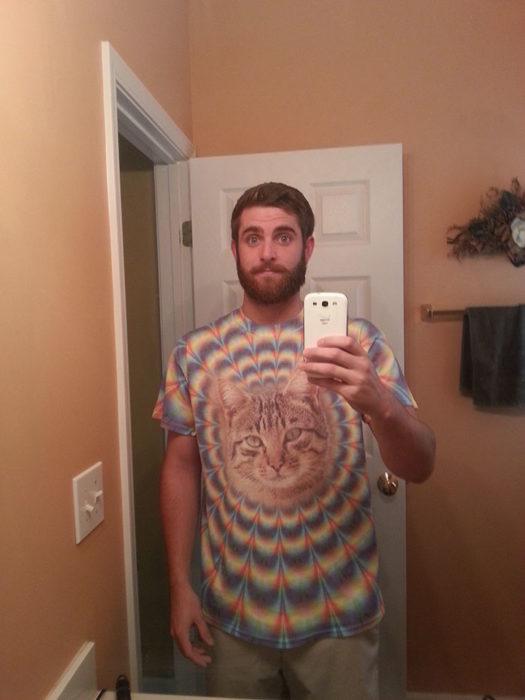 Chico usando un camisa con un gato en el pecho