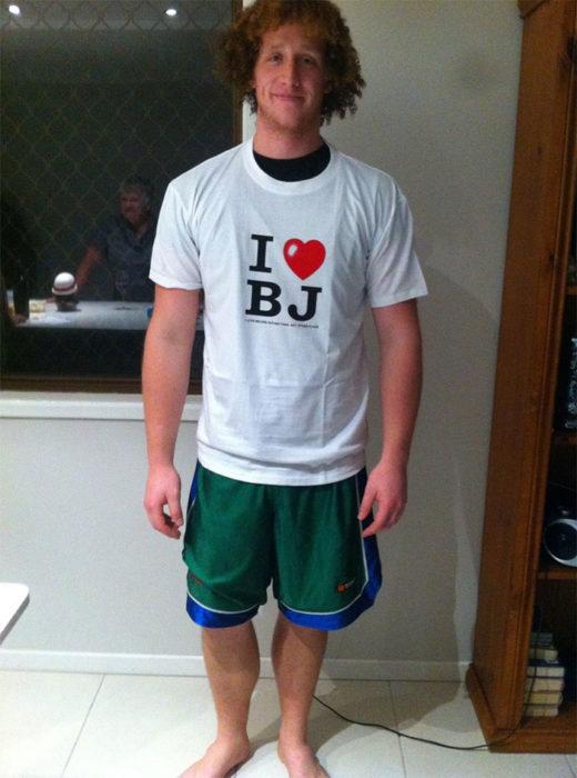 Chico parado frente a una puerta usando una camiseta horrible