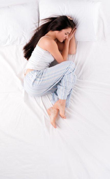 Chica durmiendo en posición fetal