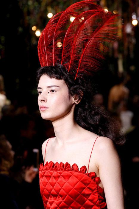 Chica usando un tocado de novia con plumas rojas