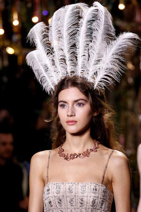Chica usando un tocado de novia con plumas blancas