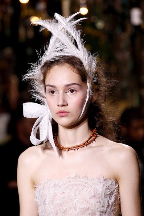 Chica usando un tocado de novia con pluma
