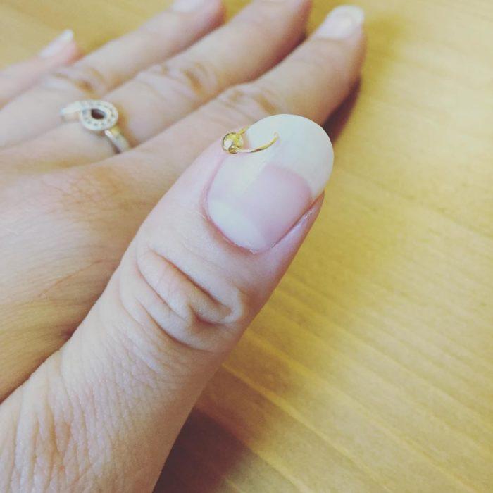 Chica con aros en la punta de sus uñas naturales