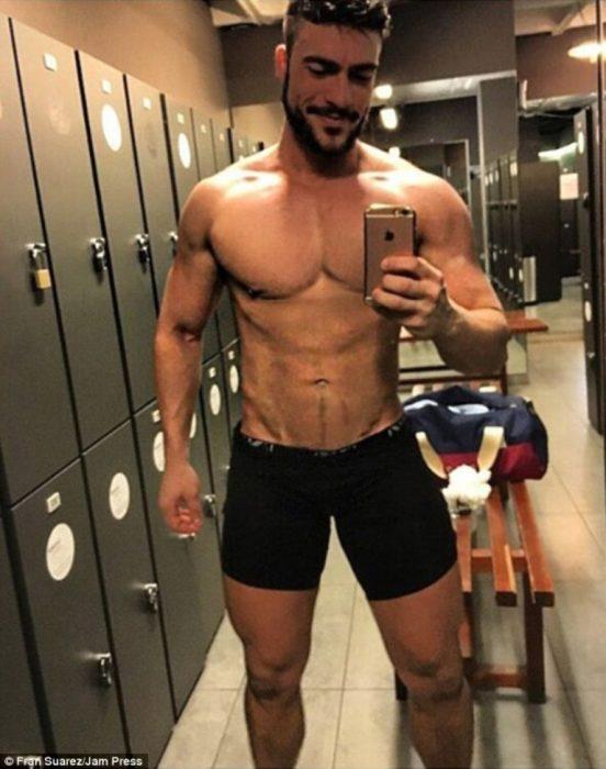 hombre con mallas cortas se toma selfie en espejo