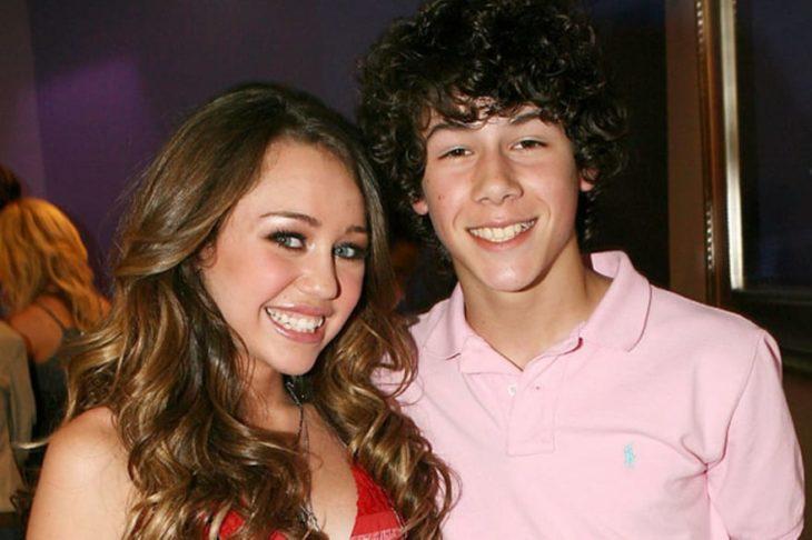 chica sonriendo y chico con camisa rosa
