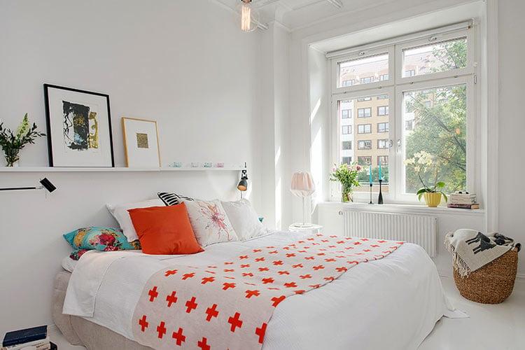 cama tendida habitación blanca con naranja