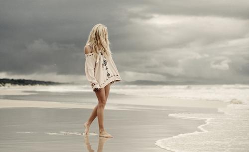 chica caminando por la playa gris
